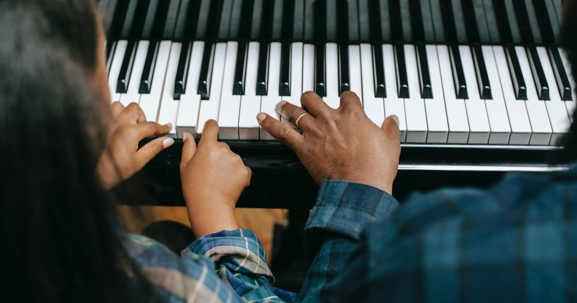 black father playing piano with daughter